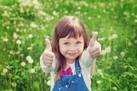 portrait of cute little girl with thumbs up shows a class on the flower meadow, happy childhood concept, child having fun, vintage toned Stockfoto