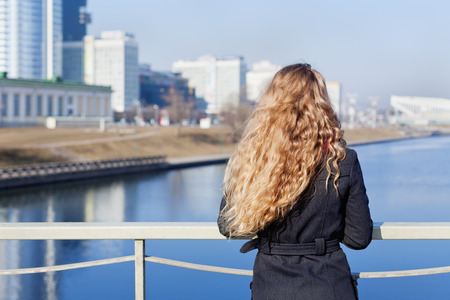 hair back: fashionable blonde woman with long curly hair standing on the bridge and looking at the river and city, back to camera Stock Photo