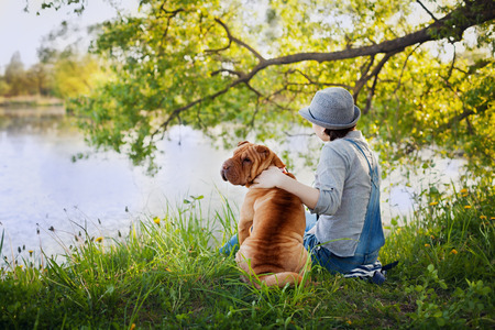 companion: young woman in a hat with dog Shar Pei sitting in the field and looking to the river in golden sunset light, true friends forever, people concept, meditation and relaxation, back to camera