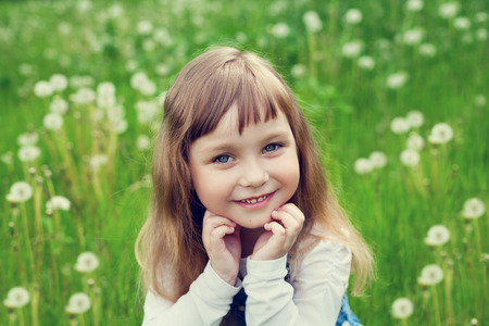 portrait of cute little girl with beautiful smile and blue eyes sitting on the flower meadow, happy childhood concept, child having fun, vintage toned photo