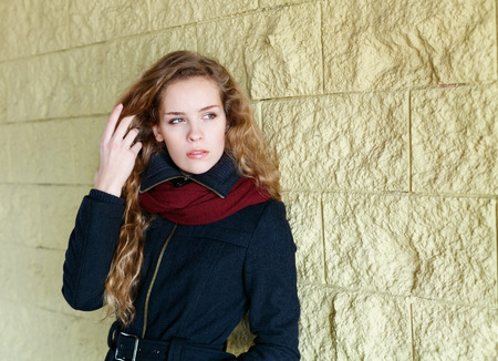 long distance: pretty young fashion woman, girl, model with long curly hair looking into the distance and posing outdoor near the wall in the street background, sensual look, warm toned