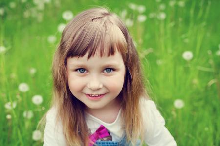 ojos azules: Retrato de la niña linda con una hermosa sonrisa y los ojos azules que se sientan en el prado de flores, concepto de infancia feliz, niño que se divierte, imagen de tonos