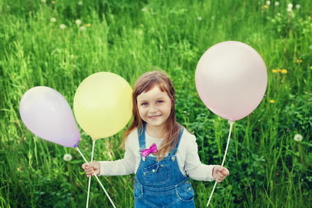 portrait of cute little girl with beautiful smile holding toy balloons in hand on the flower meadow, happy childhood concept, child having fun, vintage toned photo