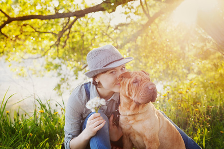happy young woman in denim overalls and hat with a bouquet of dandelions kissing her red cute dog Shar Pei on the field near the lake at sunset, true friends forever, people concept