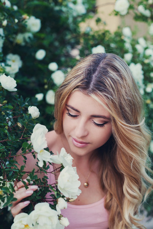 smells: beautiful woman with long curly hair smells white roses outdoors, closeup portrait of sensual girl face, blonde female portrait with flowers, elegant lady in blossom garden