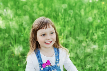 soulful eyes: Closeup emotional portrait of cute little girl with smile standing on a green meadow, happy childhood