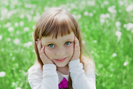 soulful eyes: Closeup emotional portrait of cute little girl with beautiful soulful eyes standing on a green meadow, happy childhood