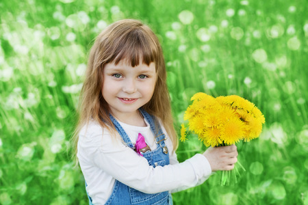 Closeup emotional portrait of cute little girl with dandelion flowers bouquet standing on a green meadow, happy childhood photo