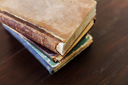 old books: Stack of old vintage books on dark wooden background, selective focus and shallow dof