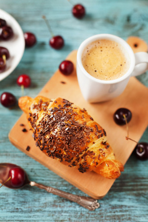 Tasty breakfast with fresh croissant, coffee and cherries on a wooden table, selective focus on croissant