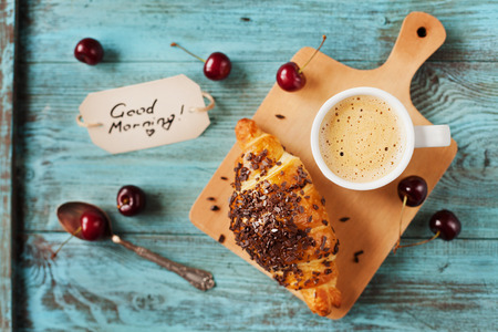 Tasty breakfast with fresh croissant, coffee, cherries and notes on a wooden table, selective focus on coffee