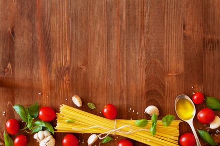 pasta: Uncooked spaghetti, cherry tomato, basil, garlic and olive oil, ingredients for cooking pasta
