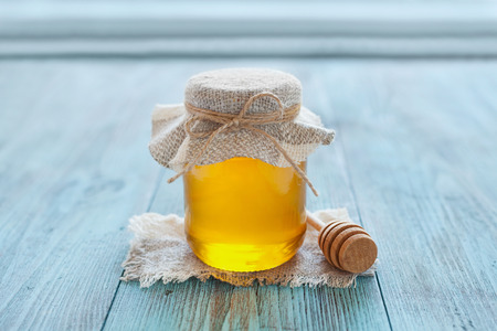 Natural honey in a pot or jar with twine tied in a bow and honey dipper on a blue wooden background