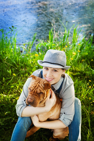 true love: Happy woman in denim overalls and hat with her dog Shar Pei sitting in the meadow near the lake at sunset, true friends forever, people pets concept Stock Photo