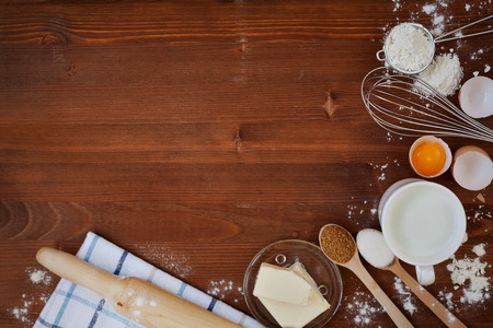 Ingredients for baking dough including flour, eggs, milk, butter, sugar, whisk and rolling pin on wooden rustic background, empty space for text, top view