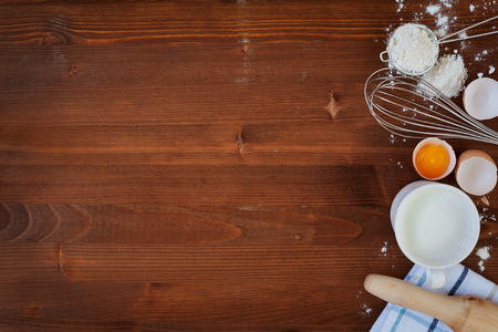 Ingredients for baking dough including flour, eggs, milk, whisk and rolling pin on wooden rustic background, empty space for text, top view