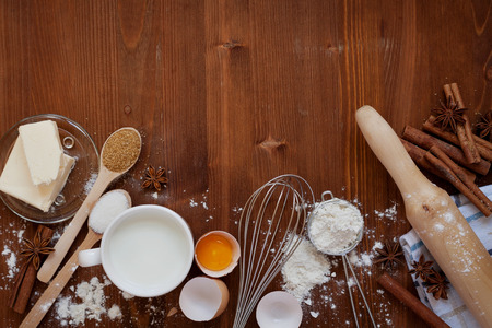 Ingredients for baking dough including flour, eggs, milk, butter, sugar, cinnamon, anise star, whisk and rolling pin on wooden rustic background, empty space for text, top view