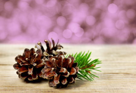 spruce: pine cones on a wooden board against christmas bokeh background