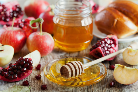 rosh: Honey, apple, pomegranate and hala, table set with traditional food for Jewish New Year Holiday, Rosh Hashana Stock Photo
