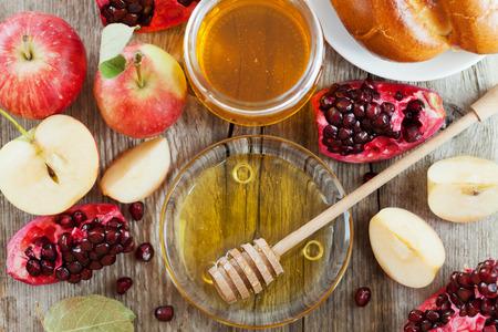 rosh hashanah: Honey, apple, pomegranate and hala, table set with traditional food for Jewish New Year Holiday, Rosh Hashana Stock Photo