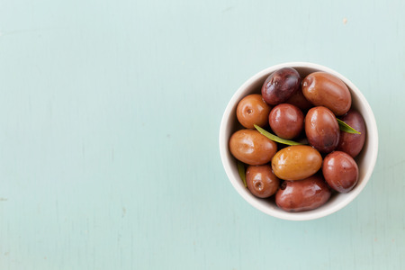 plates of food: Fresh olives in white bowl on rustic wooden table