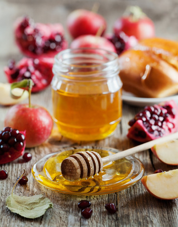 Honey, apple, pomegranate and hala, table set with traditional food for Jewish New Year Holiday, Rosh Hashana 스톡 콘텐츠