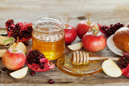 jewish background: Honey, apple, pomegranate and hala, table set with traditional food for Jewish New Year Holiday, Rosh Hashana Stock Photo