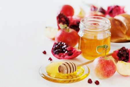 jewish: Honey, apple, pomegranate and hala, table set with traditional food for Jewish New Year Holiday, Rosh Hashana Stock Photo