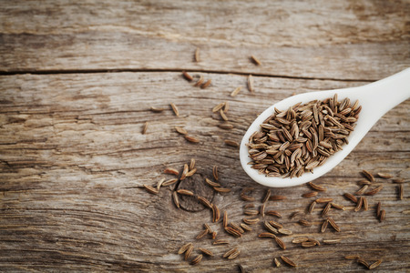 cumin: Cumin seeds or caraway in white spoon on wooden board