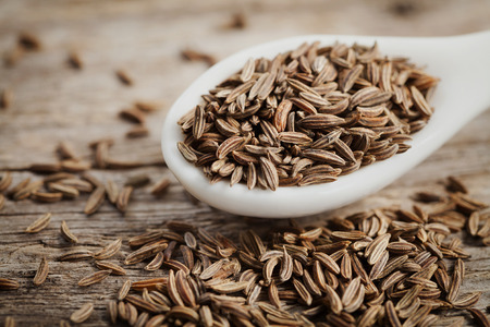 caraway: Cumin seeds or caraway in white spoon on wooden board