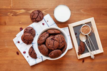 galleta de chocolate: Casera galleta de chocolate o una galleta con arándanos secos y leche en la mesa de madera, vista desde arriba