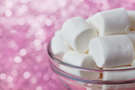 pastila: White soft marshmallows in glass bowl with pink bokeh background, selective focus Stock Photo