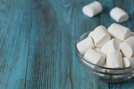 pastila: White soft marshmallows in glass bowl on blue wooden background, selective focus