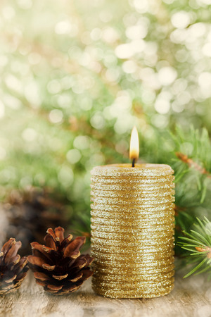 christmas candle: Christmas decorations with lighted candle, pine cones and fir branches on wooden background with magic bokeh effect, Christmas card with copy space for your text or design, selective focus