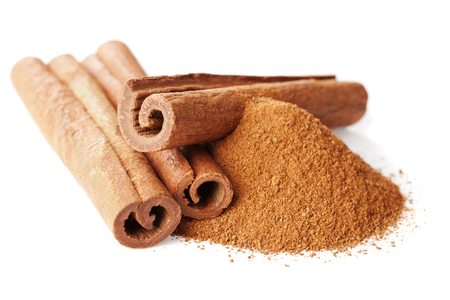 Closeup of cinnamon sticks and powder of ground cinnamon on white background Standard-Bild