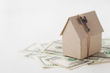 キーとドルの手形の段ボール ハウスのモデル。家の建物、ローン、不動産、住宅の新しいホームのコンセプトを買うコスト。
