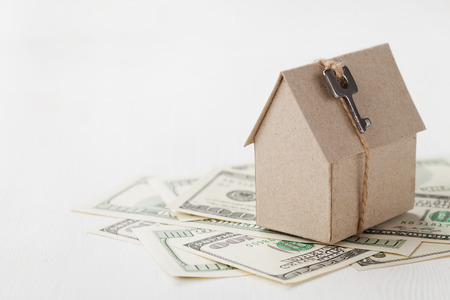 Model of cardboard house with key and dollar bills. House building, loan, real estate, cost of housing or buying a new home concept. Banque d'images