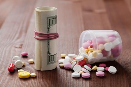 pastillas: Montón de píldoras medicinales y farmacéuticas de medicamentos dispersas desde las botellas con dinero en efectivo en dólares, el costo del medicamento y el concepto de tratamiento