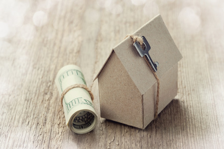 rent: Model of cardboard house with key and dollar bills. House building, loan, real estate, cost of housing or buying a new home concept. Stock Photo