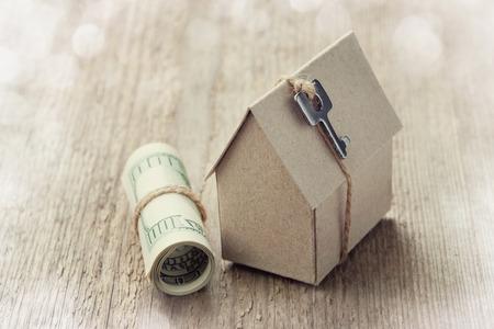 Modello di casa di cartone con le fatture chiave e dollaro. Costruzione casa, prestito, immobiliare, costo degli alloggi o l'acquisto di un nuovo concetto di casa. Archivio Fotografico - 46500589