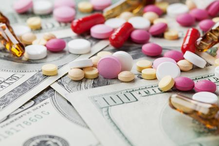 drogadiccion: Montón de píldoras farmacéuticas de drogas y medicamentos dispersas en el dinero en efectivo en dólares, el costo del medicamento y el concepto de tratamiento Foto de archivo