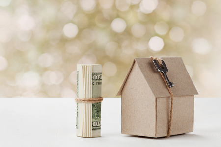 Model of cardboard house with key and dollar bills. House building, loan, real estate, cost of housing or buying a new home concept. Stock Photo