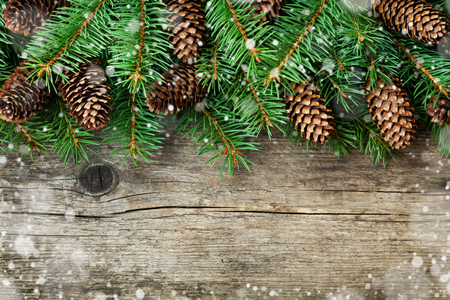 pine trees: Christmas decoration of fir tree and conifer cone on textured wood background, magic snow effect, top view Stock Photo
