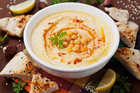 comida arabe: Hummus o houmous, aperitivo hecho de pur� de garbanzos con pasta de s�samo, lim�n, ajo, aceite de oliva, el perejil y el piment�n en mesa de madera Foto de archivo