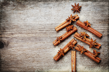 christmas cards: Christmas card with Christmas fir tree made from spices cinnamon sticks, anise star and cane sugar on rustic wooden background, vintage toned, copy space for text, top view
