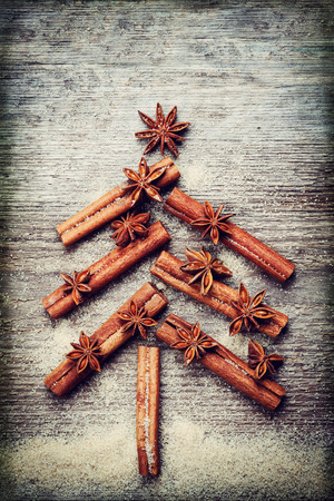 christmas spice: Christmas card with Christmas fir tree made from spices cinnamon sticks, anise star and cane sugar on rustic wooden background, vintage toned, top view