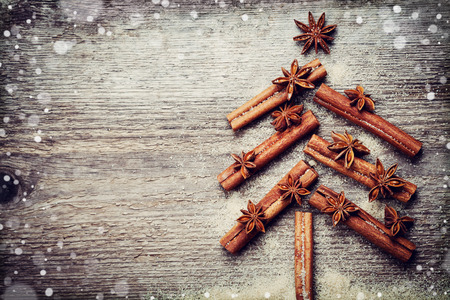 Christmas card with Christmas fir tree made from spices cinnamon sticks, anise star and cane sugar on rustic wooden background, magic snow effect, vintage toned, top view