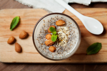 Chia seeds pudding with oat, banana and almonds decorated with mint leaves, vegetarian food