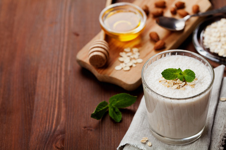almond: Healthy breakfast of banana smoothie or milkshake with oats and honey decorated mint leaves on rustic surface