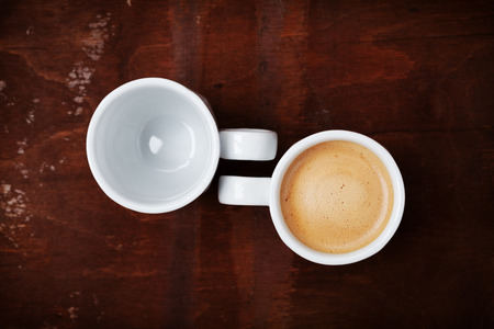 Empty and full cup of fresh coffee on rustic wooden table, benefits and harms of coffee concept, top view Stock Photo
